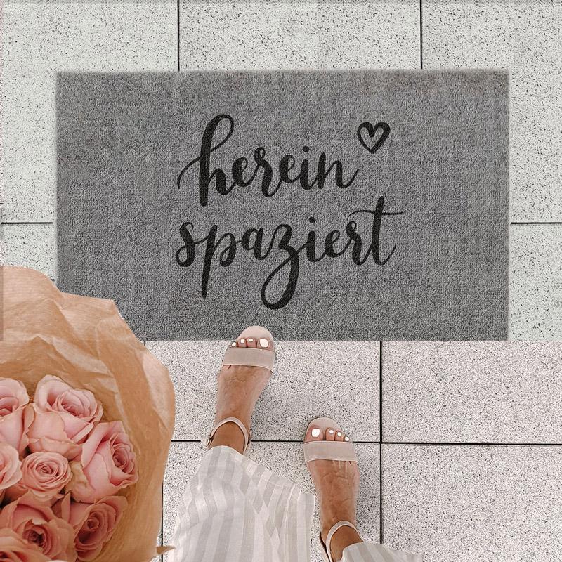 Fußmatte outdoor auf grauen Platten mit Füßen und Rosenstrauß
