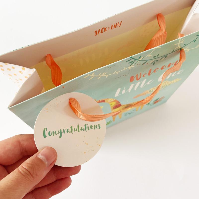 Geschenktüte-Baby-Detail Geschenkanhänger in Hand