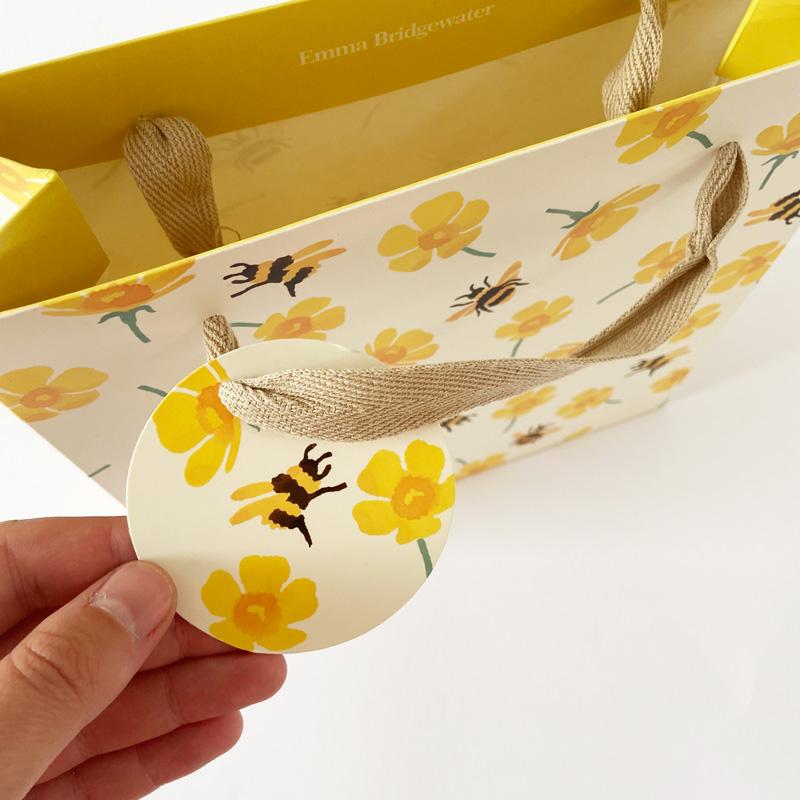 Geschenktüte-mit Bienen und Ringelblumen Geschenkanhänger im Detail in der Hand