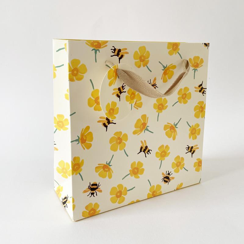 Geschenktüte-mit Bienen und Ringelblumen stehend fotografiert