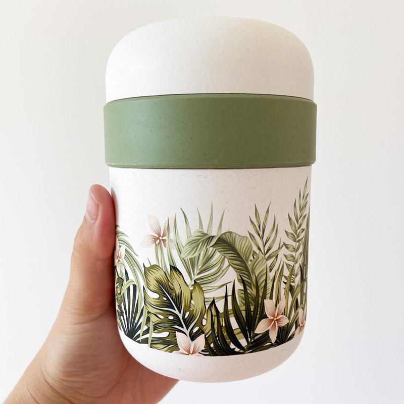Lunchpot mit grünen tropischen Pflanzen in Hand