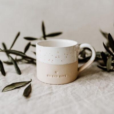 """Tasse """"No Bad Days"""" auf Baumwolltuch und grünen Blättern"""