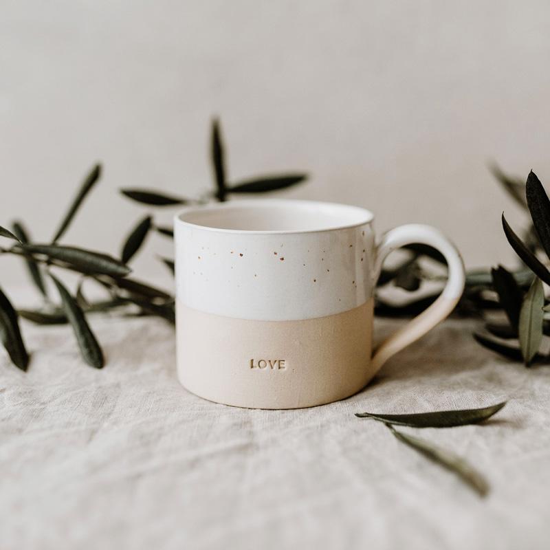 Tasse Love auf Baumwolltuch und grünen Blättern